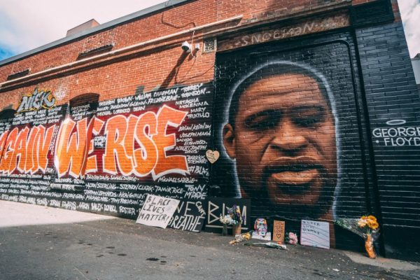 A mural on a brick building featuring George Floyd, with the words AGAIN WE RISE surrounded by names of victims of police violence.