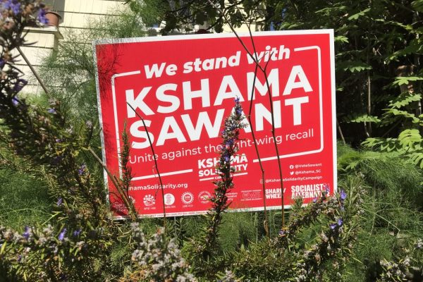"""A red-and-white picket sign surrounded by plants. It reads """"We stand with Kshama Sawant. Unite against the right-wing recall."""""""