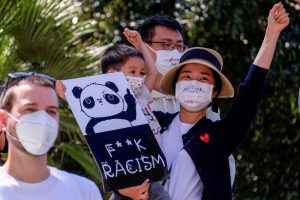 """A woman holds a child, who is holding a sign showing a panda raising its middle finger. Below it reads """"F**K RACISM. Two men are also in the photo. All are wearing filtration masks."""