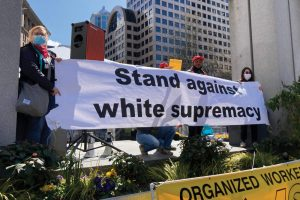 """People hold a banner reading """"Stand Against White Supremacy"""""""