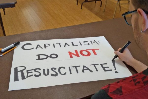 """A man finishes making a hand-lettered sign on a table that reads """"CAPITALISM: DO NOT RESUSCITATE."""""""