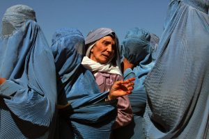 In Herat, Afghanistan, women line up to collect bags of split chick pea, wheat, and cooking oil being distributed by the UN World Food Programme (WFP).