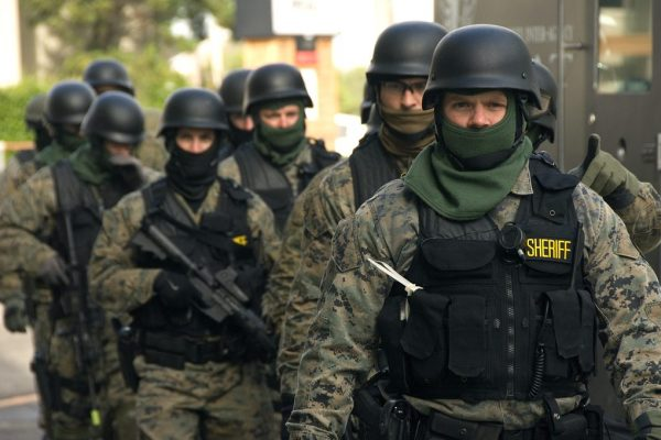 """A group wearing military-style helmets, vests, and camo, some carrying assault rifles, The lead man's vest has a """"Sheriff"""" insignia."""