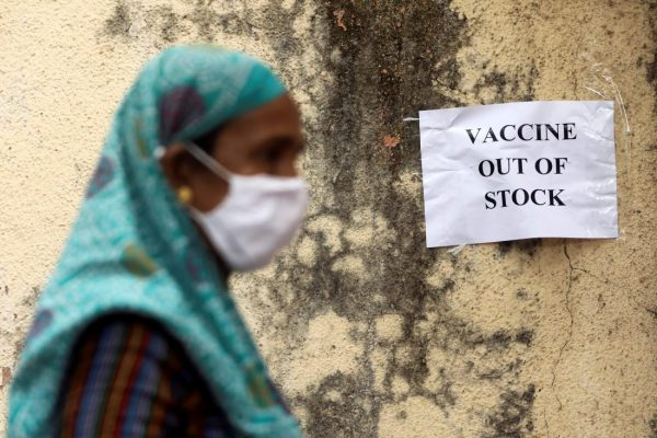 """A woman in a headwrap and medical mask walks past a sign reading """"VACCINE OUT OF STOCK."""""""