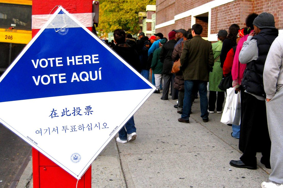 """A """"Vote Here"""" sign in four languages; a line of people from the back stand waiting."""