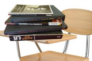 A stack of books on a school desk. Titles include The Souls of Black Folk; How to Be an Antiracist; Racism without Racists; The New Jim Crow; and Caste Class & Race.