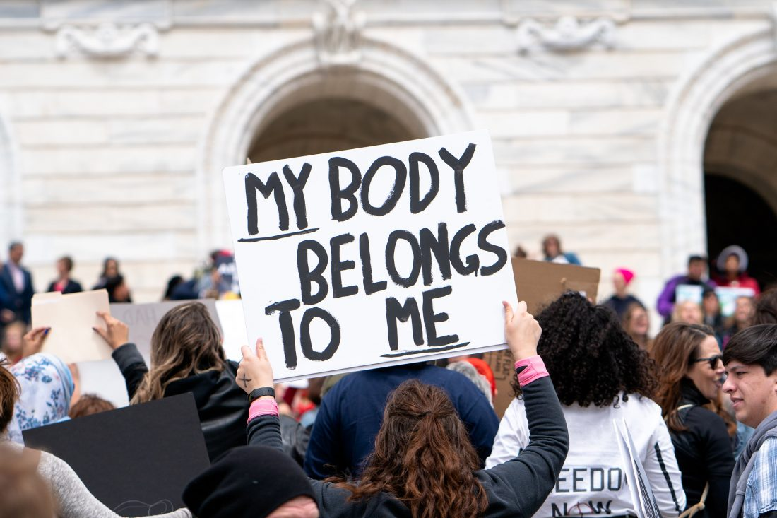 A woman holds a sign that says My Body Belongs To Me
